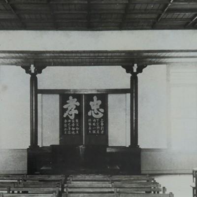 <p>講堂正面<br /> 講堂正面には、はじめ仏像が安置されていたが、中学校になるとき、視学官の指示で撤去し、寄宿舎へ奉還した。</p> <p>忠孝の二字に教育勅語による教育の理念が表象されている。講堂に歴代校長の写真を掲げたのは昭和2年からである。</p>